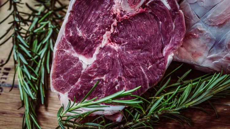 Ein Stück rohes Fleisch mit Rosmarin liegt auf einem Holzbrett