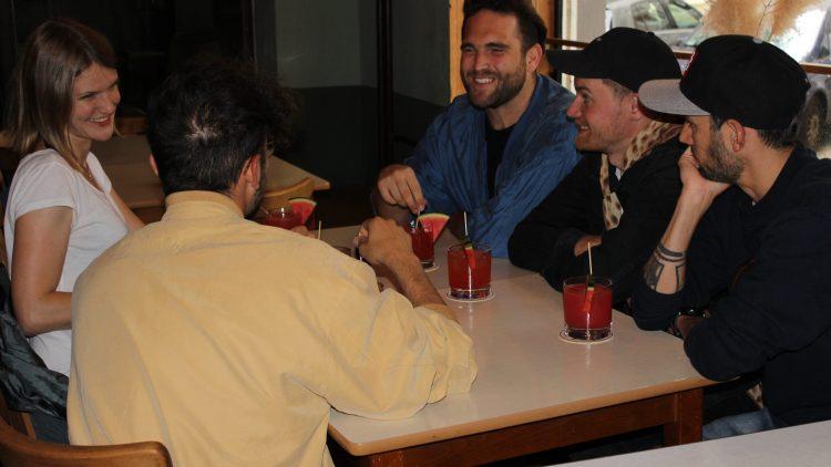 Die Band sitzt mit Cocktails am Tisch beim Interview.