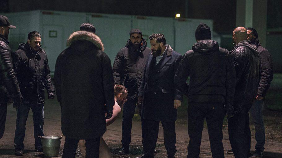 Schwarzgekleidete Männer stehen vor einem blutverschmierten Mann.
