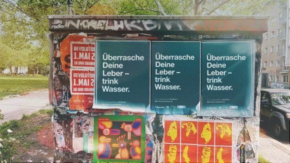 """An einem Stromkasten hängen Plakate als Werbung für Veranstaltungen, vorn ein Plakat mit dem Slogan """"Überrasche Deine Leber - Trink Wasser"""" vom gemeinnützigen Verein a tip:tap."""