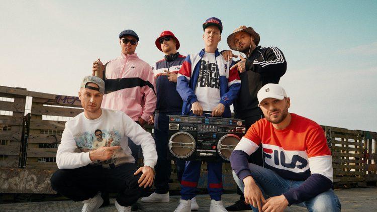 Sechs Männer sind gekleidet wie Hip-Hopper aus den Neunziger Jahren und stehen hinter oder hocken neben einem Ghettoblaster.