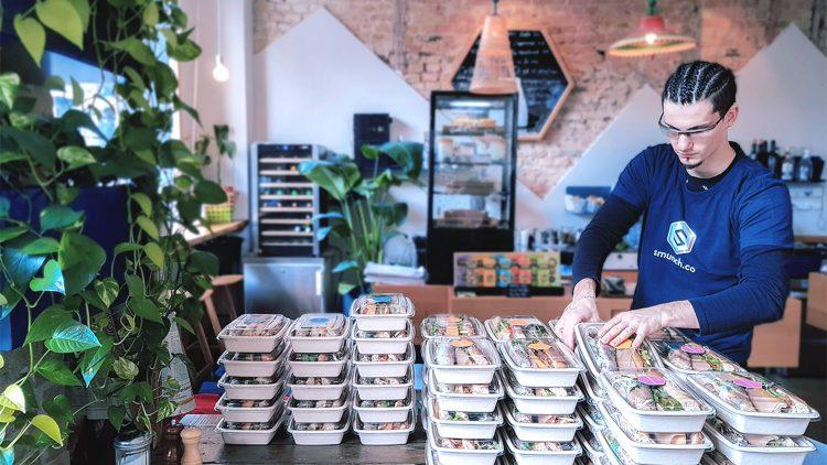 Ein Restaurantangestellter verpackt circa dreißig Lunchboxen auf einem Tisch.