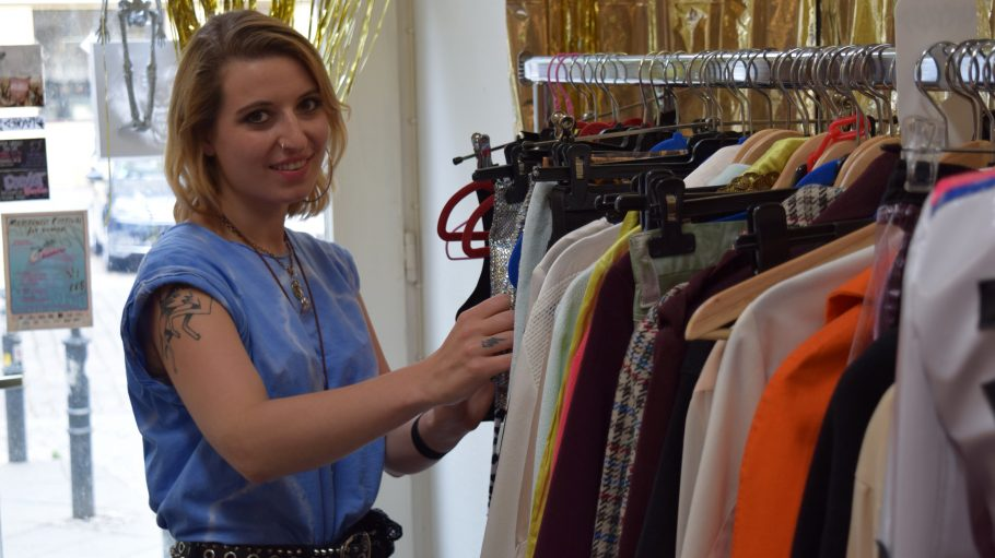 Eine junge Frau, Modedesignerin Daniela Wolf, steht neben einem Kleiderständer