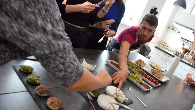 Verschiedene Menschen beugen sich über Tisch mit veganem Käse.