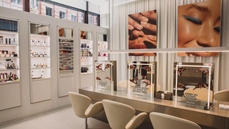 beige Ledersessel vor langen, hellen Kosmetiktischen, Nahaufnahmen von Gesichtern oder Fingernägeln auf Bildern an der Wand und Helle Regale: Die Beauty Station von Zalando in Berlins Mitte.