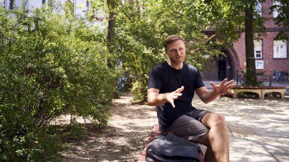 Michael Nast sitzt vor einigen Bäumen.