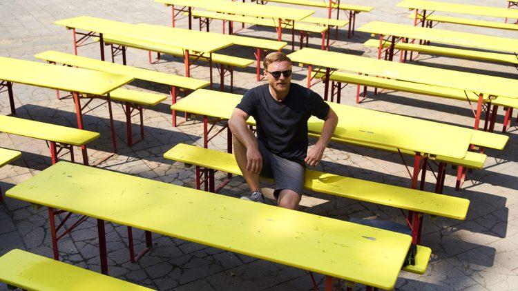Michael Nast sitzt auf den gelben Bänken im Prater.