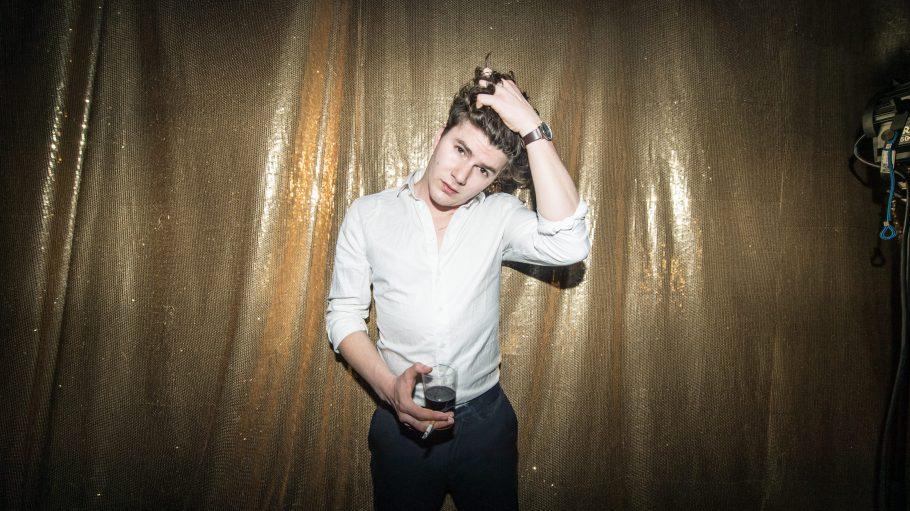 Sänger Faber mit Glas Rotwein und Zigarette in der Hand vor goldener Gardine