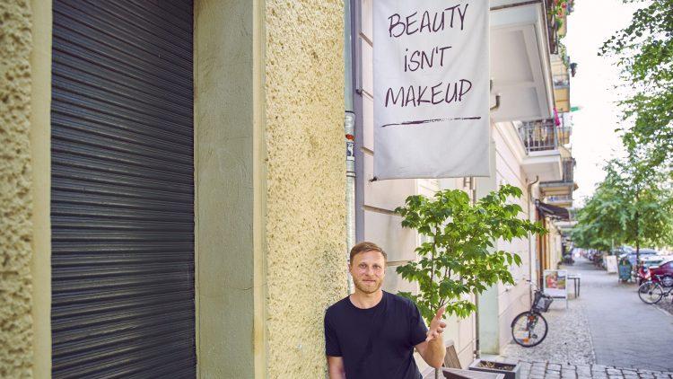 Michael Nast steht unter einer Werbung für einen Kosmetiksalon: Beauty isn't MakeUp