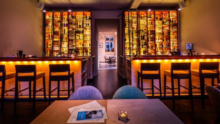 Die moderne Einrichtung der Bar mit beleuchtetem Alkoholtresen.
