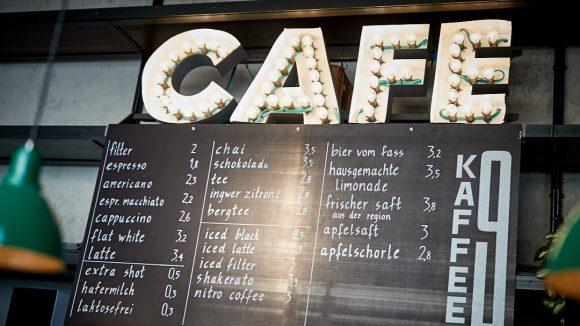 """Das Café """"Kaffee 9"""" um die Ecke von der Markthalle Neun in Kreuzberg. Eine Speisekarte mit dem Namen von dem Café."""