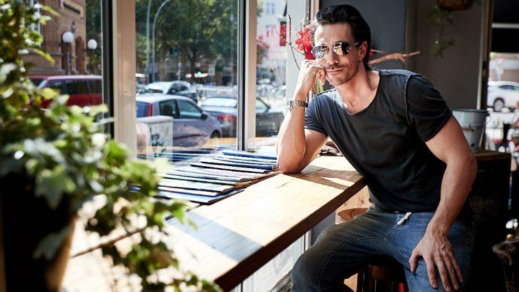Der Schauspieler sitzt im Inneren des Café Friedrichs an der Fensterbank mit Sonnenbrille und cooler Poste.