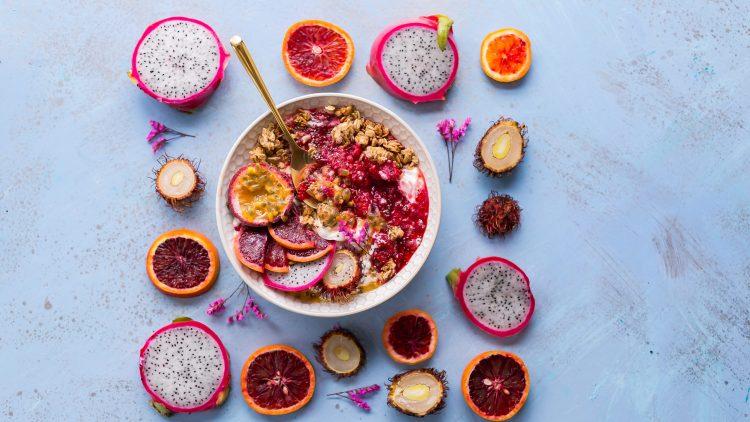 Superfood in einer Bowl mit Drachenfrucht, Orange und Wasserkastanie und Veluvia auf einem lilablassblauen Tisch.