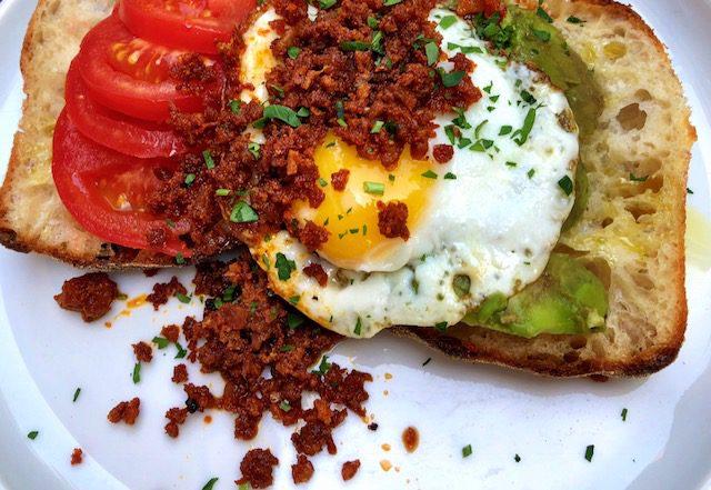 Getoastetes Brot mit Ei, Tomaten, Guacamole und Tomaten.