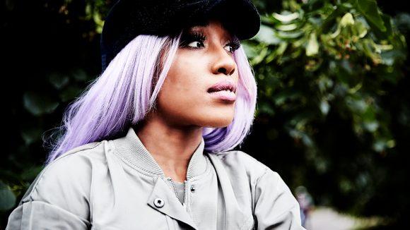 Profil von Eunique mit schwarzer Cappy, lila Haaren und langen Wimpern.