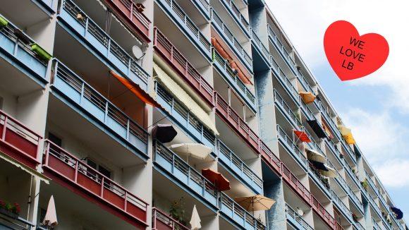 Eine Hausfront vom Plattenbau mit zahlreichen Balkonen mit Sonnenschirmen