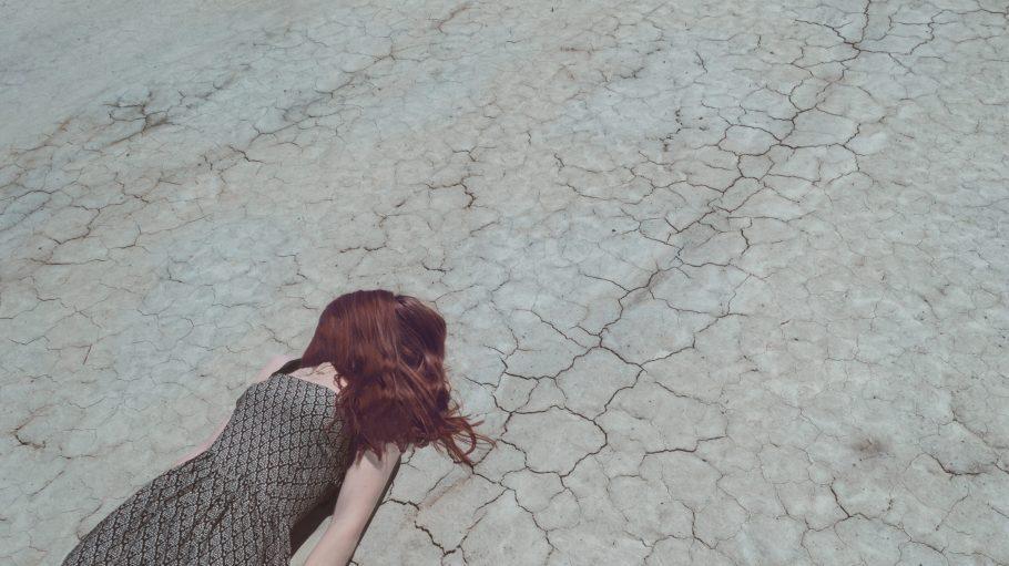 Frau mit roten Haaren liegt auf trockenem Boden