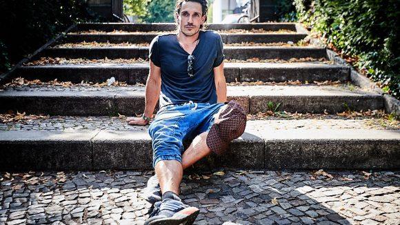 Der Schauspieler sitzt auf der Treppe im Park