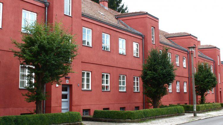 Eine rote, zweistöckige Hausfront mit kleinen Bäumen und einer kniehohen Hecke.