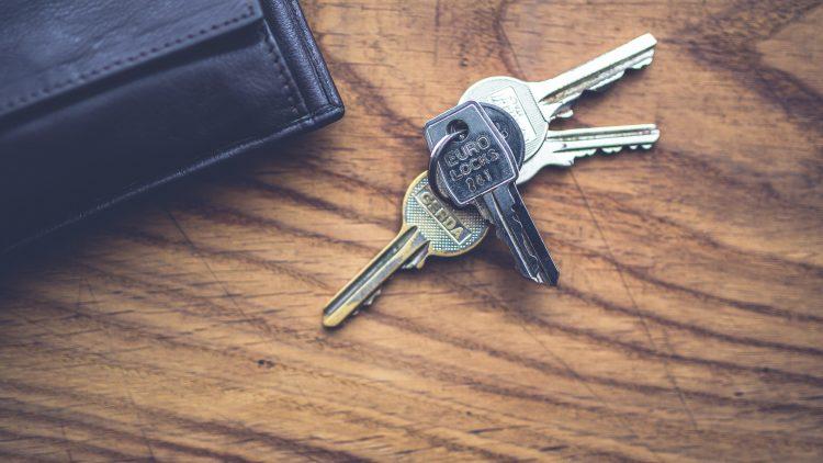 Schlüsselbund und schwarzes Lederportemonnaie auf einem braunen Holztisch vom Schlüsseldienst Berlin.