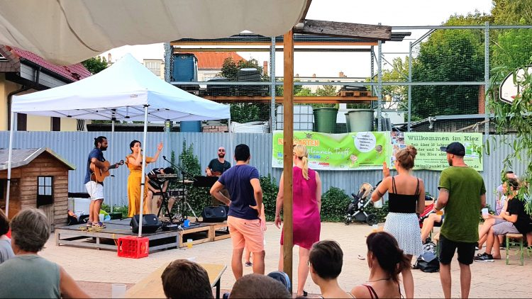 Im Hintergrund eine kleine Bühne mit Sängerin, Schlagzeug, Gitarrenspielern. Im Vordergrund junge Menschen im Sitzen oder Stehen, der Bühne zugewandt.