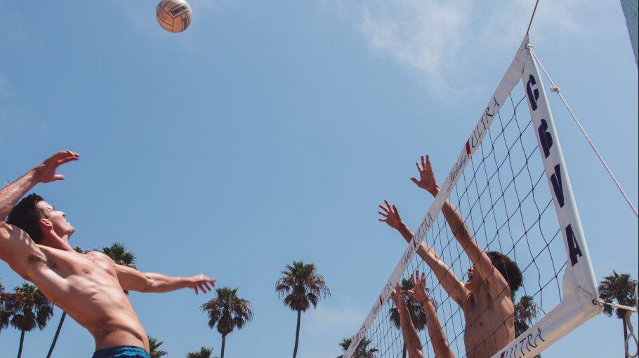 Ein Mann mit kurzer Hose und nacktem Oberkörper springt in die Luft und holt aus, um einen Volleyball über ein Netz zu schlagen. Dort springen gegnerische Spieler in die Luft und setzen zum Block an.