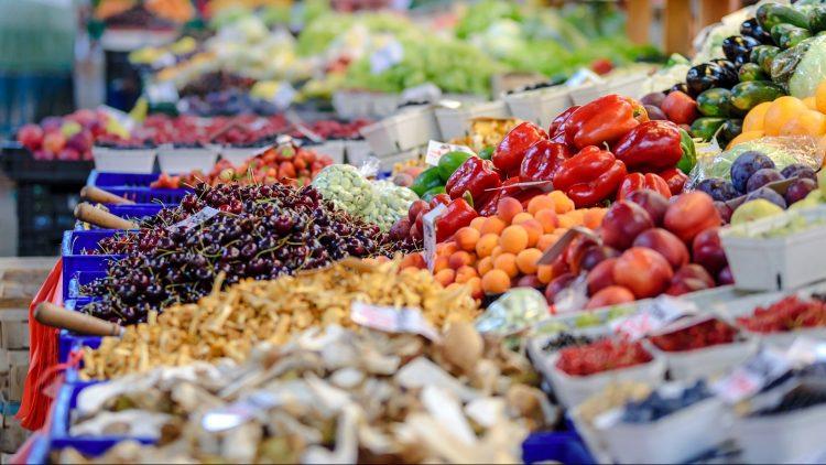Ein Marktstand mit einer Auslage bunter Obst- und Gemüsesorten.