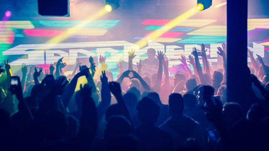 Menschen stehen vor einen DJ-Pult. Im Hintergrund bunte Bilder