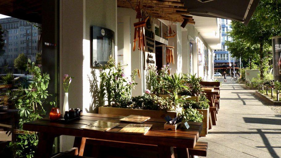 Außenansicht des Restuarants. Holzbänke und bepflanzte Kästen vor einer weißen Hauswand. Über der Tür Bambushalme und Windspiele, darüber eine schwarze Markise. Blick die