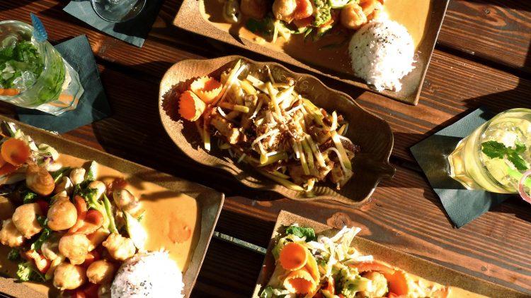 Ein Holztisch voller Speisen und Getränke von oben aufgenommen. In der Mitte eine Schale mit einem Mangosalat, drum herum Teller mit Gemüse und Reis sowie Cocktailgläser.
