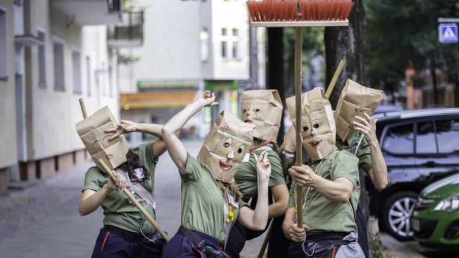 Eine Theatertruppe mit Mülltüten auf dem Kopf und Besen in der Hand.