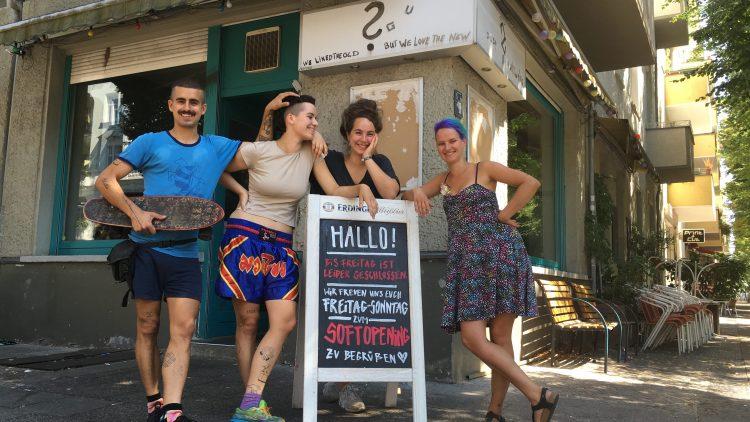 vier junge Leute stehen um ein Schild herum, auf dem für ein Soft-Opening geworben wird. Im Hintergrund die graue Fassade eines Eckhauses.