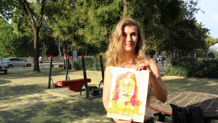 Die Künstlerin steht im Park und zeigt ihr gerade eben gezeichnetes Bild vor sich.