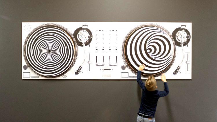 Eine Wandplatte mit zwei Kreisen mit schwarz-weißen Mustern, die einem Schallplattenspieler nachempfunden ist. Davor ein kleiner Junge, der die Platten dreht.