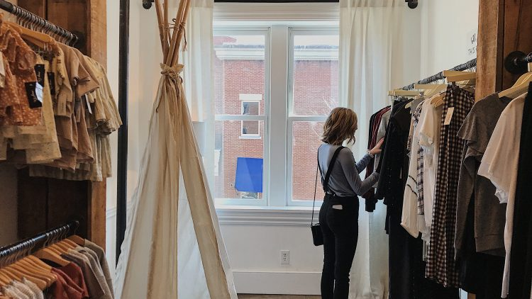 Frau in einem hellen Klamottenladen schaut durch die Kleider an der Kleiderstange
