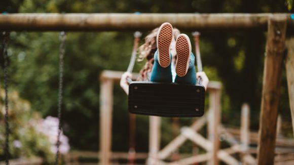 Ein junges Mädchen auf einer Schaukel, schwingt in Richtung der Kamera