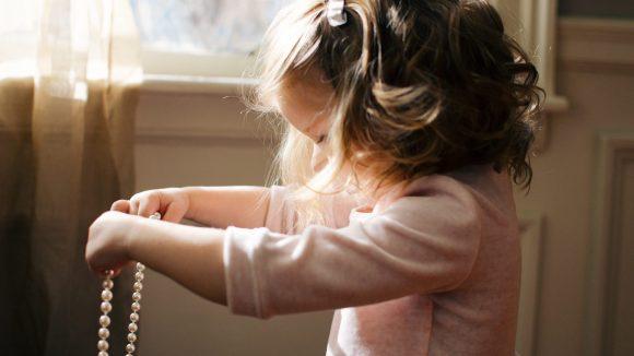 Kleines Mädchen mit blonden Haaren, rosa T-Shirt und rosa Schleife im Haar mit einer Perlenkette in der Hand beim Secondhand-Shopping.