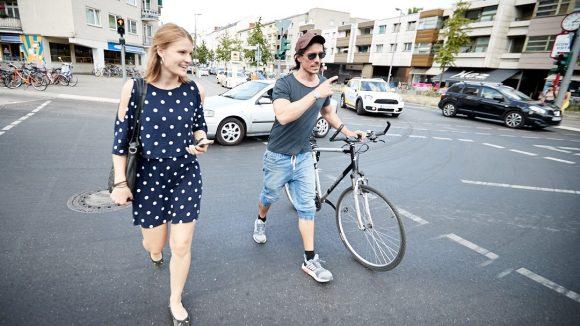 Reporter und Schauspieler gehen redend über die Straße.