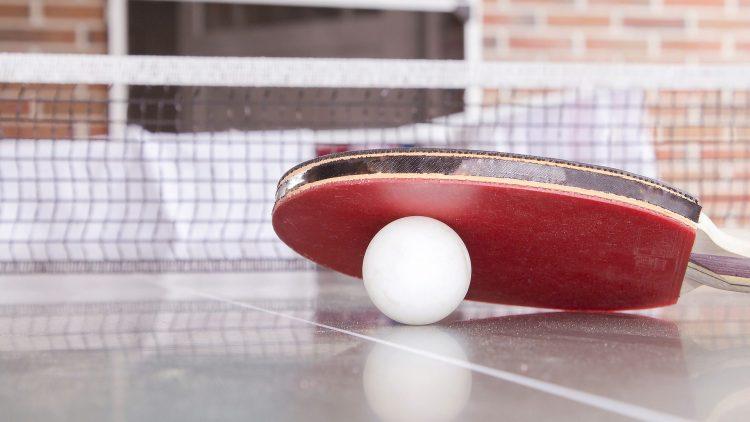 Ein Tischtennisschläger liegt auf einem Ball auf einer Tischtennisplatte.
