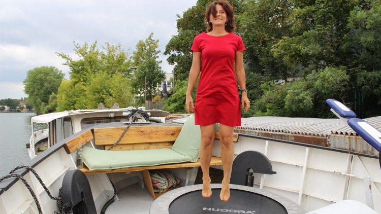 Kerstin Hack im roten Kleid springt auf dem Trampolin.
