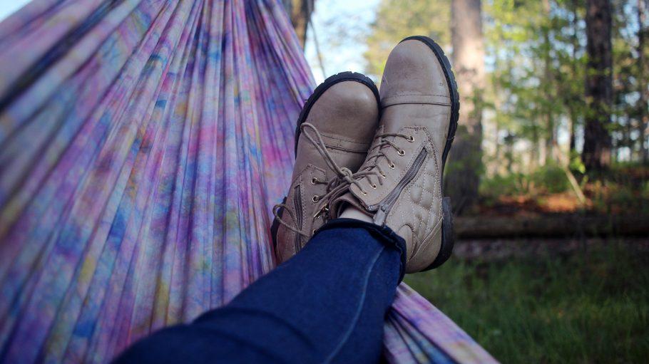 Beine in Jeans und Füße in leichten Stiefeln in einer bunten Hängematte im freien. Im Hintergrund eine Wiese und Bäume.