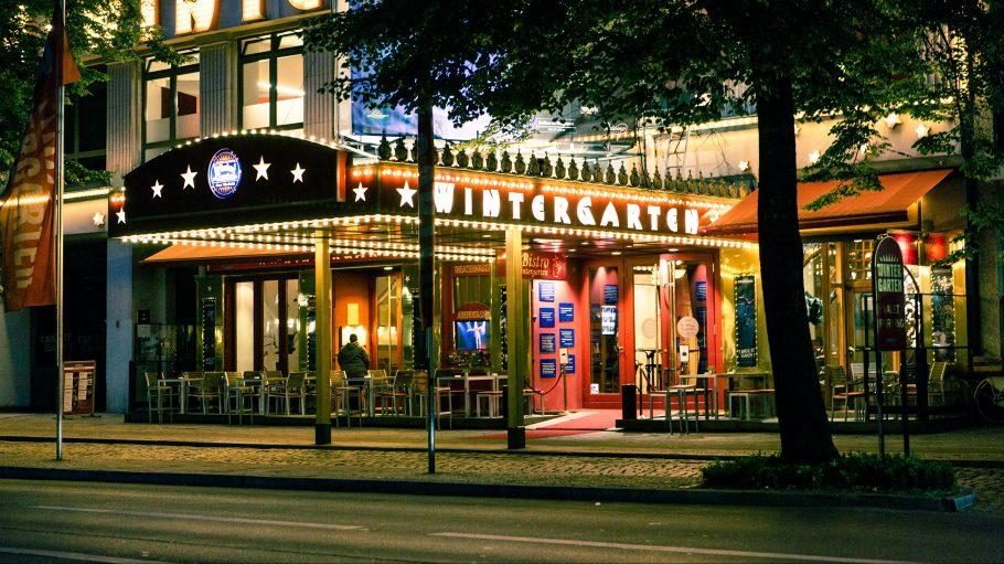 Außenansicht des Berliner Theater's Der Wintergarten nachts. Ein überdachter Eingangsbereich, erleuchtet von Deko-Lampen, mit rotem Teppich und Sitzmöglichkeiten.