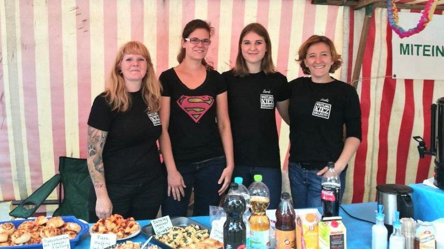 Vier Frauen in schwarzen T-Shirt an einem überdachten Stand. Vor ihnen Speisen und Getränke