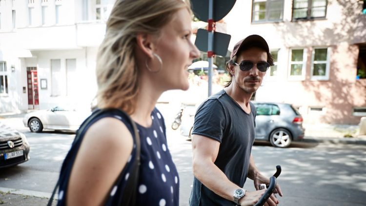 Die Journalistin vorne, der Schauspieler dahinten mit seinem Fahrrad:: Seitenaufnahme