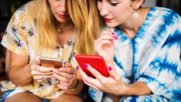 zwei junge frauen schauen auf ihr smartphone