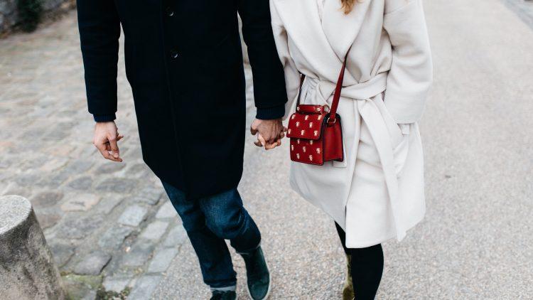 Ein Paar läuft über die Straße und hält Händchen