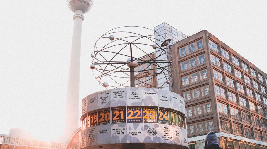 Weltzeituhr und im Hintergrund Berliner Fernsehturm im Abendlicht