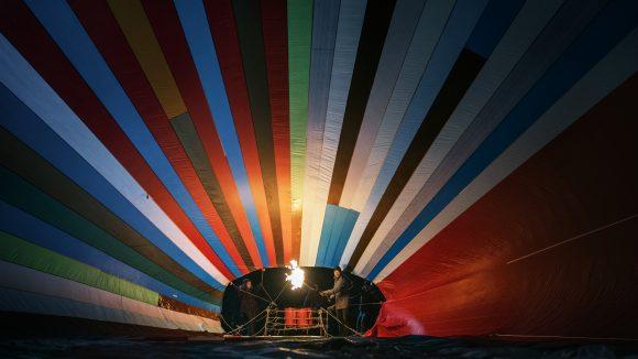 Ein bildfüllender Heißluftballon entfaltet sich kurz vor dem Start. Ein Mann heizt ihn mit einer Gasflamme auf.