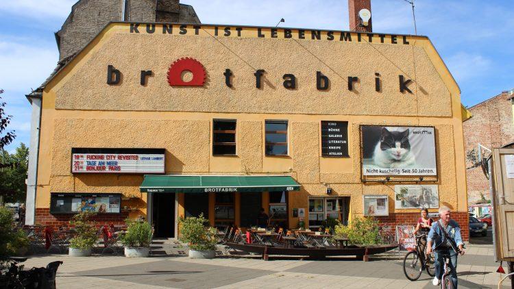 Kulturzentrum Brotfabrik in Weißensee von außen bei Sonnenschein mit Tischen vor dem Eingang