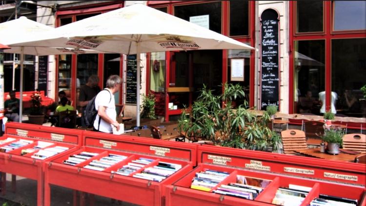 Das Café Tasso in der Frankfurter Alle mit einer großen Auslage von gebrauchten Büchern in roten Boxen, die vom kostenlosen Abhol-Service weiterverkauft werden für einen guten Zweck.
